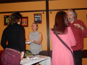 Amy hands over a book while Ken Rodgers of Kyoto Journal discusses coming issues